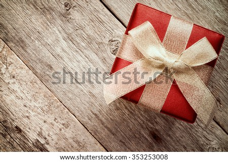 Top view of giftbox with golden  bow on a wood background - stock photo