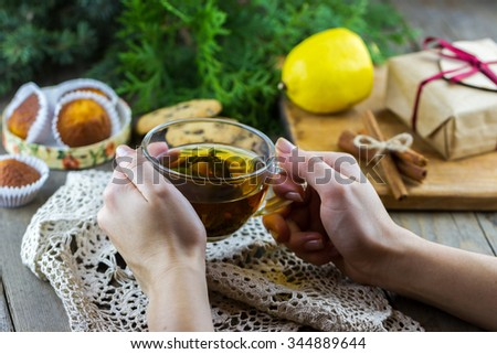 Top view of glass cup of tea with mint in female hand. Homemade chocolate chip cookies, lemon, cinnamon sticks, gift box and thuja branches on wooden background - stock photo
