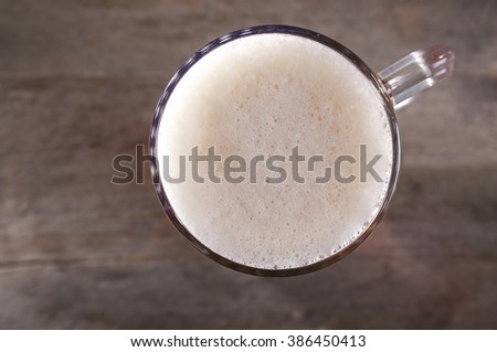 Top view of glass mug of light beer with foam on wooden table, close up