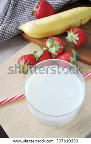 Top view of glass of milk with fresh fruits on wooden background
