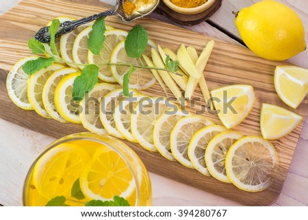 Top view of glass with ginger, fresh mint, lemons infused turmeric water and cut ingredients on cutting board.