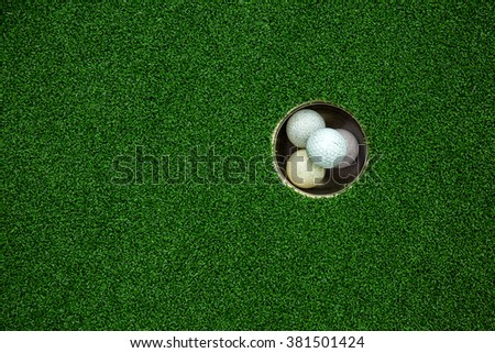 Top view of golf balls stacked up in green field - stock photo