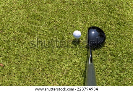 Top view of golf driver and ball on tee - stock photo