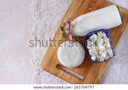 top view of greek cheese , bulgarian cheese and milk on wooden table over wooden textured background. Symbols of jewish holiday - Shavuot