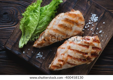 Top view of grilled chicken breasts and green salad, close-up