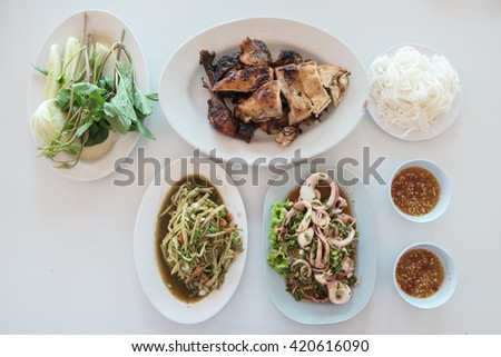 Top view of grilled chicken, squid spicy salad, bamboo shoot spicy salad, thai vermicelli, spicy sauce and fresh vegetables - stock photo