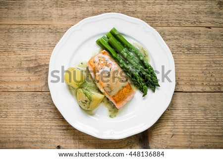 Top view of grilled salmon fillet with potatoes and asparagus garnished with dill sauce arranged on white plate and old wooden table - stock photo