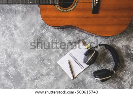 Top view of Guitar with headphone,pen and notebook on grunge background