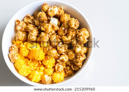 top view of half cheese and half caramel popcorn in white bowl - stock photo