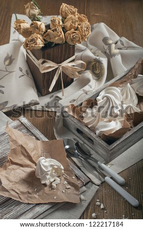 Top view of half of meringue and crumbs on paper, wooden box with meringues and dry roses in square vase on dark wooden background - stock photo