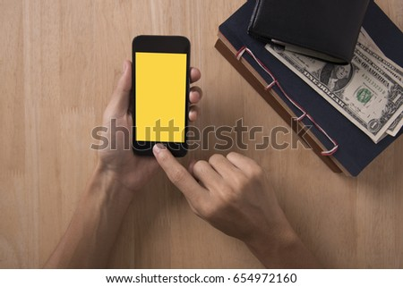 Top view of hand holding smart phone with yellow blank screen on wood desktop.