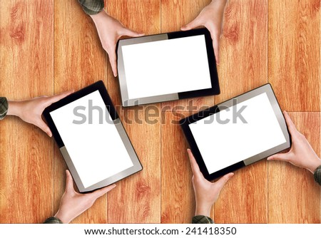 Top View of Hands Holding Three Digital Tablet Computers with Blank White Screens as Copy Space over wooden background - stock photo