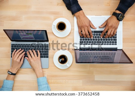 Top view of hands of man and woman working with two laptops and drinking coffee on wooden table - stock photo