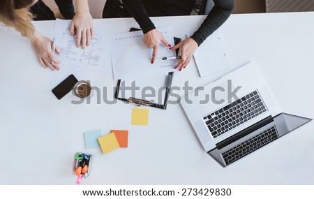 Top view of hands of two business woman analyzing financial data. Coworkers working on chart at desk in office. - stock photo