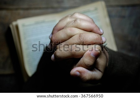 Top view of hands praying with a bible in a dark over wooden table. - stock photo