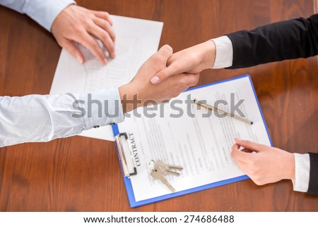 Top view of handshake of a real estate agent and a client. - stock photo