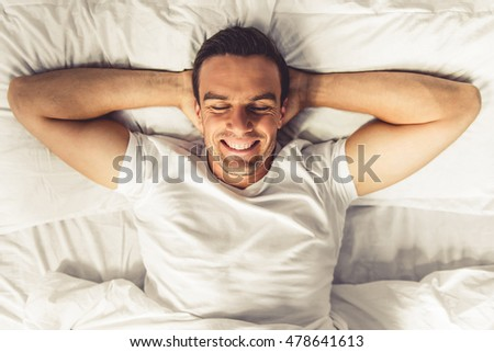 Top view of handsome man smiling while lying with closed eyes and hands behind head in his bed at home