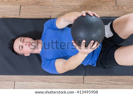 top view of Handsome muscular man doing sit-ups on a wooden floor. - stock photo