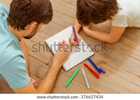 Top view of handsome young father and his cute little son drawing while lying on a wooden floor in the room - stock photo