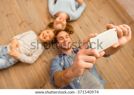 Top view of handsome young father making selfie with his beautiful family while lying on wooden floor at home. - stock photo
