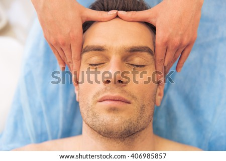 Top view of handsome young man getting a face massage, lying with closed eyes