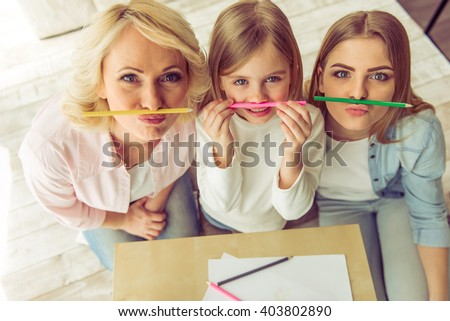 Top view of happy beautiful granny, her daughter and granddaughter posing with colorful pencils and looking at camera - stock photo