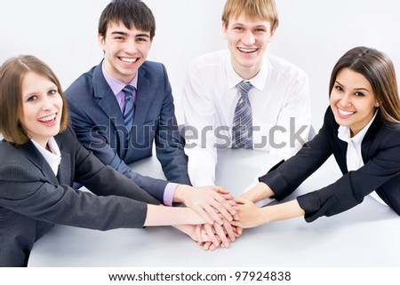 Top view of happy business team with their hands together gesturing unity - stock photo
