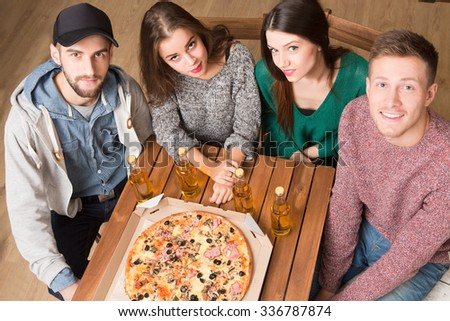 Top view of happy company of best friends resting in pizzeria. Two men and two women looking at the camera and smiling for photographer. - stock photo