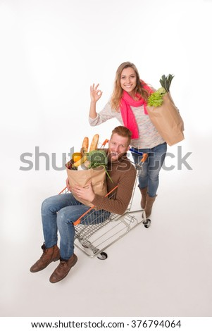 Top view of happy couple after shopping. Handsome man lying in shopping cart and holding bags while girl-friend standing near. - stock photo