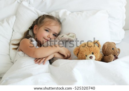 Top view of happy cute awaking girl with her toy animals, bedtime, childhood and family concept, close-up indoor portrait
