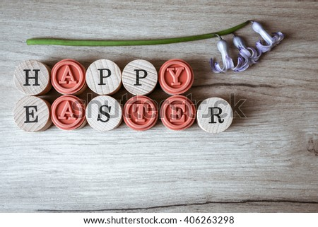 Top view of happy easter text and flower decoration on wooden background - stock photo