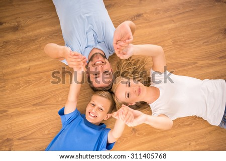 Top view of happy family are smiling to the camera, lying on the floor. - stock photo