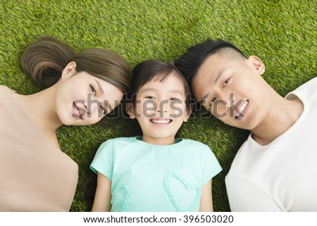 top view of Happy  Young  Family lying on the grass - stock photo