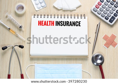 Top view of Health Insurance with notebook, stethoscope, hypodermic syringe, plaster, gauze, medicine, tape and calculator. - stock photo