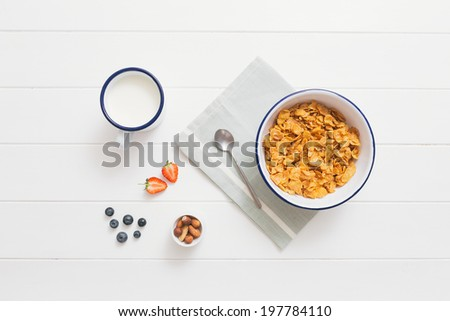 Top view of healthy breakfast with cereals, berries, honey and nuts in an enamel bowl on a white wood background - stock photo