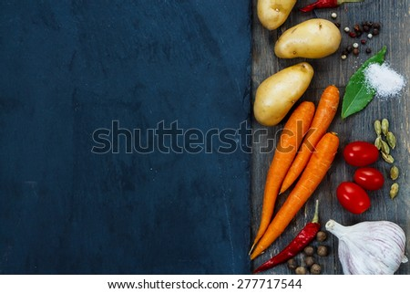 Top view of Healthy eating background with fresh organic vegetables, spices and herbs over slate. Healthy food from garden.  - stock photo