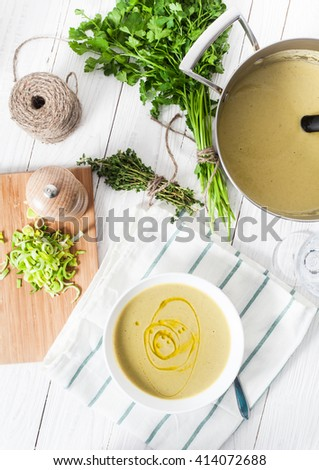 Top view of healthy, low-cal, diet vegetable potato and leek soup based  served in white bowl with olive oil. White wood background. Steel pot with soup, parsley, peppermill and glass of water on back - stock photo