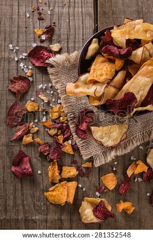 Top view of healthy vegetable beetroot, sweet potato and white sweet potato chips over rustic background - stock photo