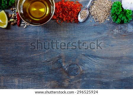 Top view of herbs, spices, olive oil, salt and lemon on dark wooden background with space for text. Food and cuisine ingredients. - stock photo