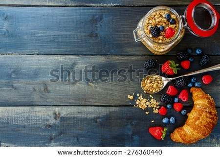 Top view of homemade granola in glass jar, fresh berries and croissant for breakfast on dark wooden table. Health and diet concept. Background with space for text. - stock photo