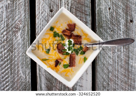 Top view of homemade organic potato leek soup with Greek yogurt, Applewood smoked bacon, shredded cheddar cheese, and garlic chives on a weathered barn wood table - stock photo