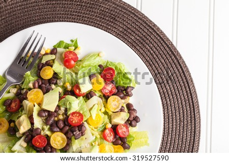 Top view of homemade southwest black bean lime salad with corn, cherry tomatoes, lettuce, avocado, and black beans with vinaigrette dressing for clean eating - stock photo
