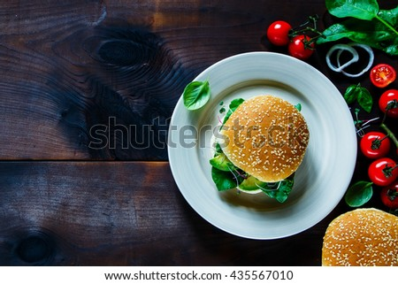 Top view of homemade vegetarian sandwich with avocado, tomatoes, spinach, basil and sprout on ceramic plate over old wood dark background, copy space. - stock photo