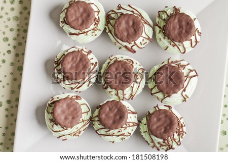 Top view of Irish Mint Cupcakes - Chocolate cake with thin chocolate mint cookie pieces filled with mint topped with green mint buttercream frosting, a dark chocolate drizzle, and mint cookies - stock photo