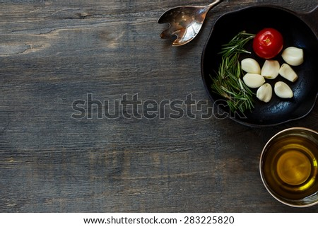 Top view of Italian ingredients in vintage cast iron skillet on rustic wooden background. Vegetarian food, health or cooking concept. - stock photo