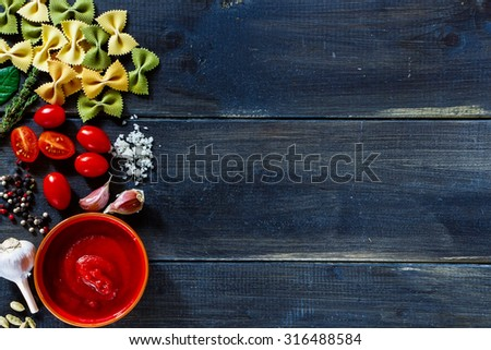 Top view of italian pasta ingredients (cherry tomatoes, pasta, garlic, fresh herbs, spices) on dark wooden background with space for text. Vegetarian food, health or cooking concept.  - stock photo