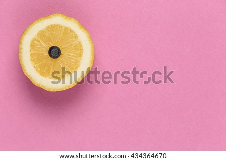 Top view of juicy lemon and blueberries inside. Fruit duo on a pink background. Background with space for text. Fruits, citrus, diet and objects concept - ripe orange or lemon slice. - stock photo