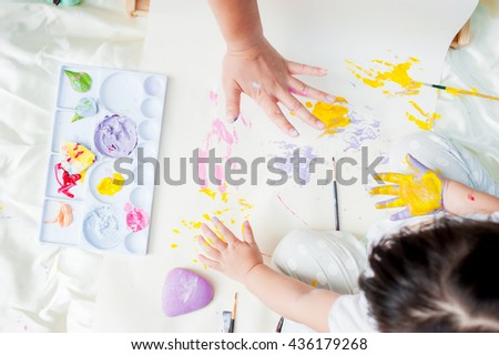 Top view of kid and his mother painting with watercolor paints on the paper.