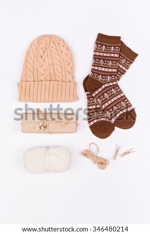 Top view of knitted hat, socks, gift box and wool yarn. Winter themed objects shot from above on white background. - stock photo