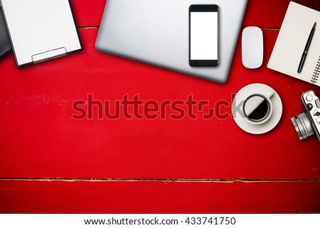 Top view of laptop and smart phone empty white screen material office desktop on red wooden desk. - stock photo